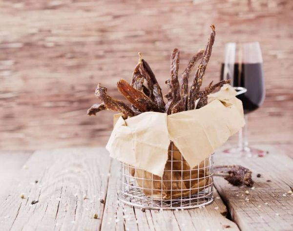 Biltong chilli bites in a basket with wine
